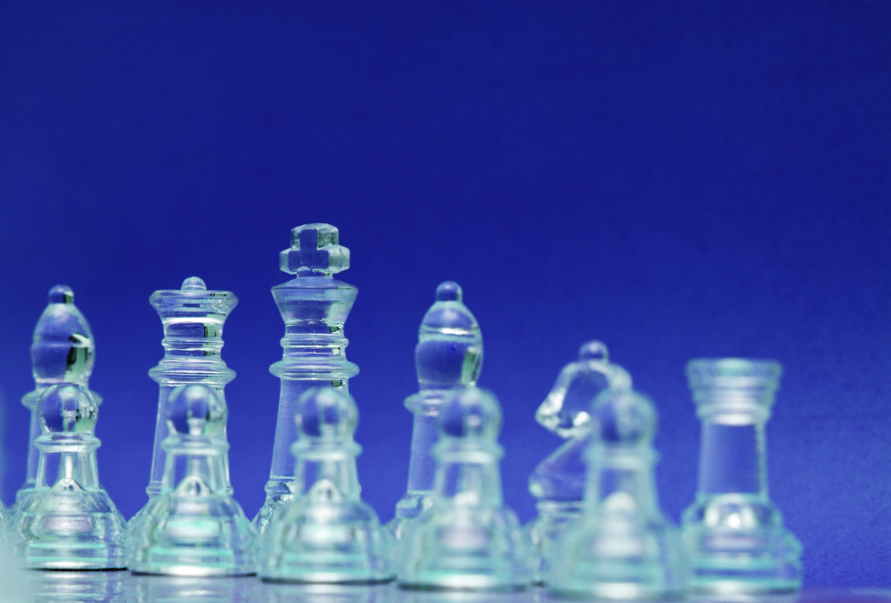 glass chess figures over the blue background